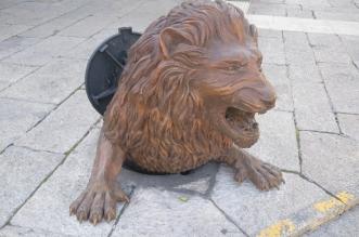 Escultura León saliendo de la alcantarilla